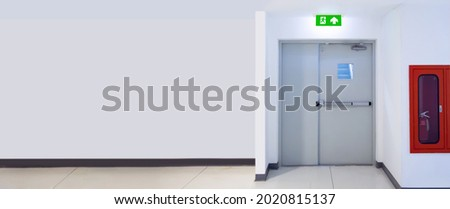 Green emergency fire exit sign or fire escape with the doorway or door exit and fire hose cabinet in the building for evacuation in the event of a fire and safety prevent or prevention and rescue.