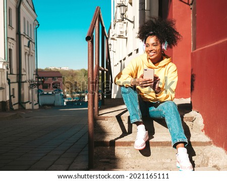 Beautiful black woman with afro curls hairstyle.Smiling model in yellow hoodie.Sexy carefree female enjoying listening music in wireless headphones.Posing in the street at sunset.Holds smartphone