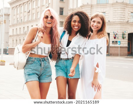 Three young beautiful smiling hipster female in trendy summer clothes.Sexy carefree multiracial women posing on the street background.Positive models having fun in sunglasses. Cheerful and happy Royalty-Free Stock Photo #2021165189