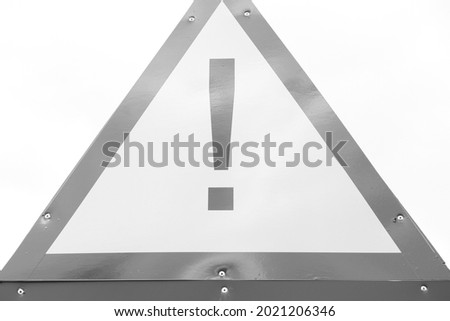 Warning triangular red and yellow hazard sign, taken outside and without Photoshop. Black and white image.