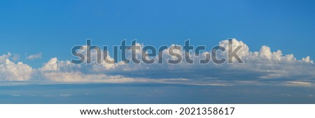 Panorama of a cloudy sky with cumulus clouds and place for text from above on a light blue background. Wide horizontal sky landscape and beautiful skyline for weather banner. Royalty-Free Stock Photo #2021358617