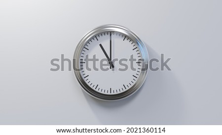 Glossy chrome clock on a white wall at eleven o'clock. Time is 11:00 or 23:00 Royalty-Free Stock Photo #2021360114