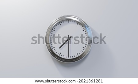Glossy chrome clock on a white wall at half past seven. Time is 07:30 or 19:30 Royalty-Free Stock Photo #2021361281