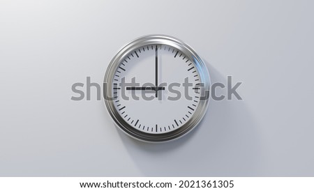Glossy chrome clock on a white wall at nine o'clock. Time is 09:00 or 21:00 Royalty-Free Stock Photo #2021361305