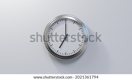 Glossy chrome clock on a white wall at seven o'clock. Time is 07:00 or 19:00 Royalty-Free Stock Photo #2021361794