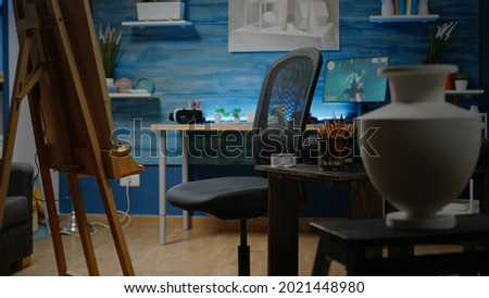 Empty creativity studio space with white canvas and easel for professional drawing. Nobody in artwork room but craft tools, colorful pencils, vase and equipment for creative design Royalty-Free Stock Photo #2021448980