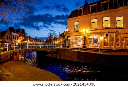 A bridge across the river in the evening city. City river bridge in evening scene. Lights in evening city Royalty-Free Stock Photo #2021454038