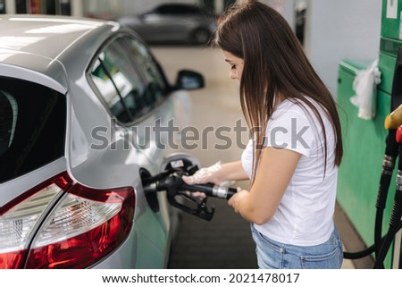 Attractive young woman refueling car at gas station. Female filling diesel at gasoline fuel in car using a fuel nozzle. Petrol concept. Side view Royalty-Free Stock Photo #2021478017