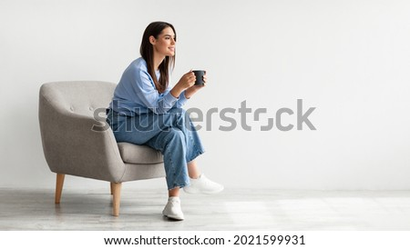 Full length of young woman drinking hot coffee in cozy armchair against white studio wall, banner design with free space. Peaceful lady having relaxing day, chilling on lazy morning Royalty-Free Stock Photo #2021599931