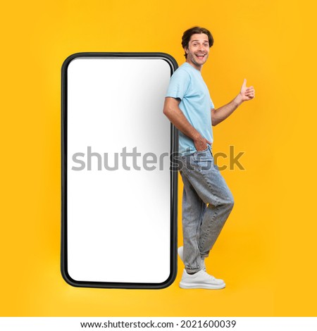Excited Man Leaning On Big Smartphone With Blank White Screen And Gesturing Thumb Up Sign, Cheerful Guy Recommending New App Or Website, Standing On Yellow Background, Mock Up Image, Full Body Length Royalty-Free Stock Photo #2021600039