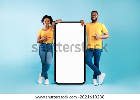 Great mobile app. African American couple pointing at giant smartphone with mockup, promoting application or website, advertising product or service, blue background. Full length Royalty-Free Stock Photo #2021610230
