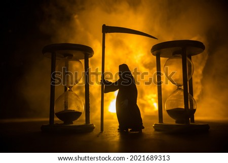 Time concept. Scary view of grim reaper silhouette standing between hourglasses with smoke and lights on a dark background. Surreal decorated picture