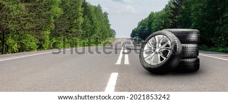 summer tires and alloy wheels set on an asphalt road. tire change season, auto trade, copy space panorama Royalty-Free Stock Photo #2021853242