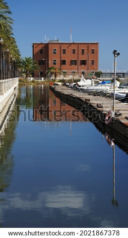 in the port of Olbia a rectangular tiled building reflects into the seawater forming a square box next to the towed graphic boats. Sardinia, Italy