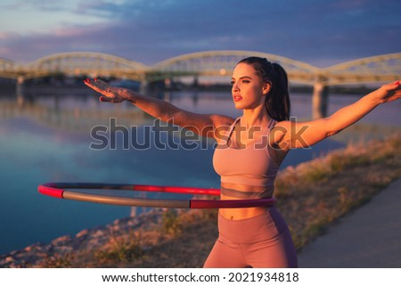 Young woman doing hula hoop exercise at riverside in sunset Royalty-Free Stock Photo #2021934818