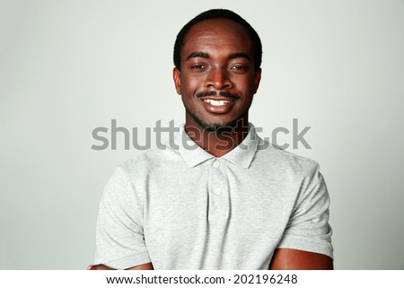 Portrait of a smiling african man on grya background #202196248