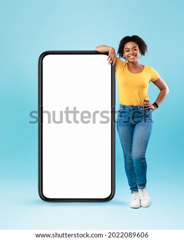 Happy black woman leaning on big smartphone with blank white screen, smiling at camera on blue studio background, mockup for mobile app, website, your advertisement design Royalty-Free Stock Photo #2022089606
