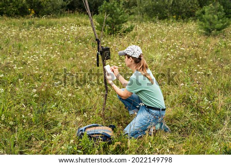 Young woman scientist zoologist writing down data from trap camera to notepad, observing wild animals in taiga forest, monitoring of rare and endangered animal species, World Wildlife Day ecology Royalty-Free Stock Photo #2022149798