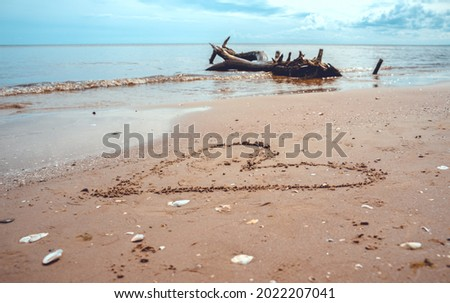 A drawing of a heart on a yellow sand at a beautiful seascape background. Royalty-Free Stock Photo #2022207041