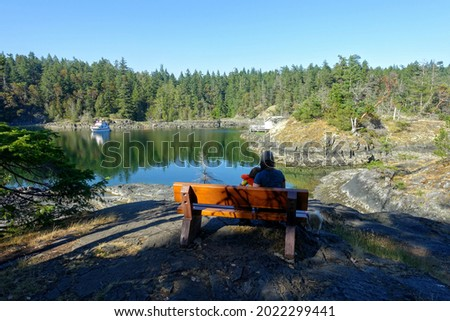 A mother and daughter sitting side by side on a wood bench overlooking a beautiful serene cove surrounded by rocky shore and forests in Smugglers Cove, Sunshine Coast, British Columbia, Canada
