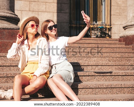 Two young beautiful smiling hipster female in trendy summer clothes.Sexy carefree women posing in the street. Positive models having fun, hugging.They taking photo selfie. Sitting at the stairs
