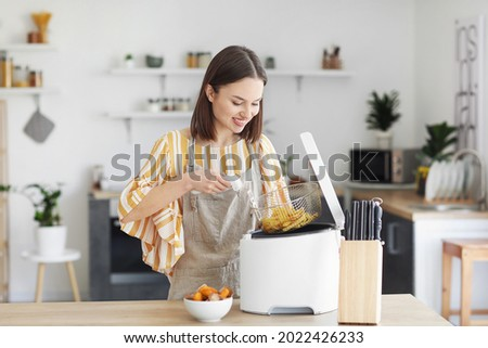 Young woman taking tasty french fries from deep fryer in kitchen Royalty-Free Stock Photo #2022426233