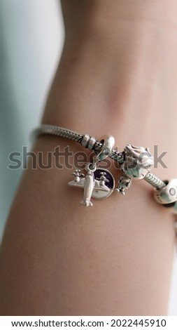silver Charm bracelet close up  with cute boy travel charm Royalty-Free Stock Photo #2022445910