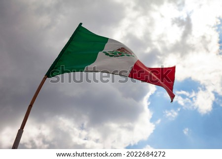 mexican flag flying on a flagpole in a mexican house. Mexico independence day concept Royalty-Free Stock Photo #2022684272