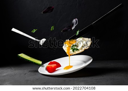 Fried egg levitation. Dark food photo. A chicken egg with liquid yolk, leaves of basil, dill, cucumber falls on a white plate. Breakfast creative concept.