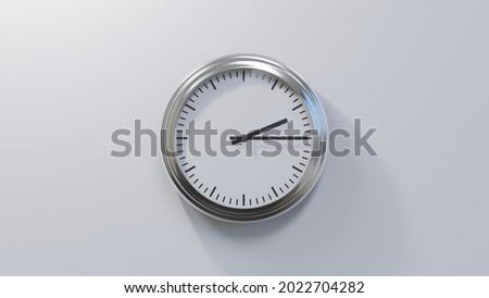Glossy chrome clock on a white wall at quarter past two. Time is 02:15 or 14:15 Royalty-Free Stock Photo #2022704282