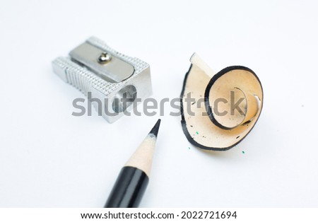 Sharpener and a broken pencil. Shavings and a graphite on white background. Close up, Macro photo. Back to school concept. Royalty-Free Stock Photo #2022721694
