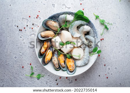 Mixed frozen seafood in plate on a gray stone background. Raw Shrimp, mussels and scallops Royalty-Free Stock Photo #2022735014