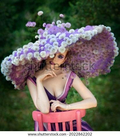 Photoshoot girl and dandelions. Lady in a hat made of dandelions. Glamorous beauty in a lilac hat. Lilac makeup. Fantasy image. Young model and dandelions  Royalty-Free Stock Photo #2022862202