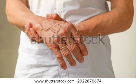 an old man support his arms which pain,numbness,weakness,paralysis concept of Guillain barre syndrome caused by autoimmune disorder