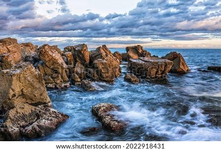 Waves beat against the coastal sea rocks. Coastal sea rocks. Sea rocks view Royalty-Free Stock Photo #2022918431