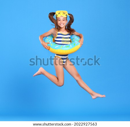 Little funny happy girl in swimsuit and goggles on her head jumping up in air with inflatable ring around waist, isolated over blue studio background. Summertime, vacation an school holidays concept Royalty-Free Stock Photo #2022927563