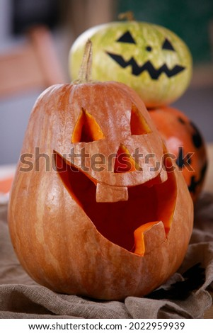 Pumpkin Jack o Lantern with carved smile. Close up of a pumpkin with a carved smile on the table, and in the back there are two more pumpkins with scary faces painted. Vertical shot. Royalty-Free Stock Photo #2022959939