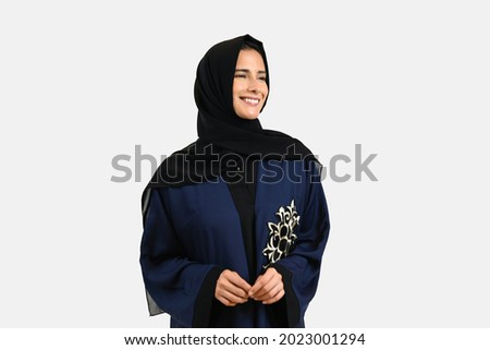 Half body shot of woman in Hijab Abaya looking far away the camera. Beautiful female wearing cultural outfit common in the Emirates. Portrait of Emirati lady with fair skin tone Royalty-Free Stock Photo #2023001294