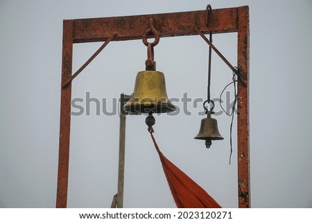 Stock photo of two ancient copper or bronze bell hanging on a orange color iron frame at hindu temple on blur foggy background. Picture captured at sateri hill station Kolhapur ,Maharashtra, India.