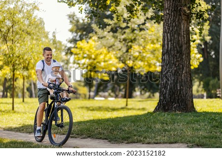 An active family day in nature. A father and son ride a bike through the woods on a sunny summer day. A cute boy is sitting in a bicycle basket while he rides a bicycle. They enjoy the ride Royalty-Free Stock Photo #2023152182