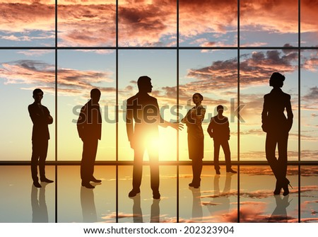 Silhouettes of businesspeople standing against panoramic office window #202323904