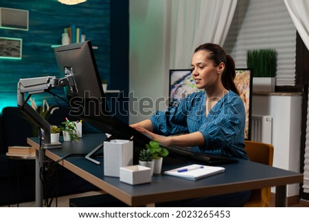 Photo editing specialist working as graphic designer at office doing retouching work on pictures using editor interface, template software. Woman with modern photography equipment