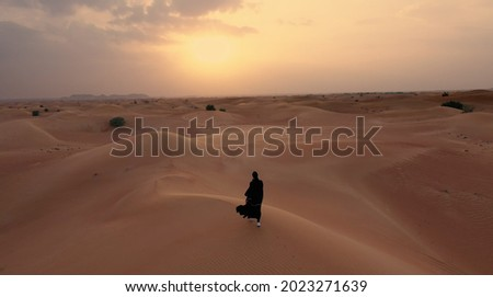 AERIAL. Camera following woman in traditional Emirati dress walking in a desert in strog wind and sunset. Royalty-Free Stock Photo #2023271639