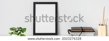 Desk arrangement. Workplace. Mockup frame. Empty wall of copy space. Books and notebooks on the desk. Banner. Panorama. Royalty-Free Stock Photo #2023276328