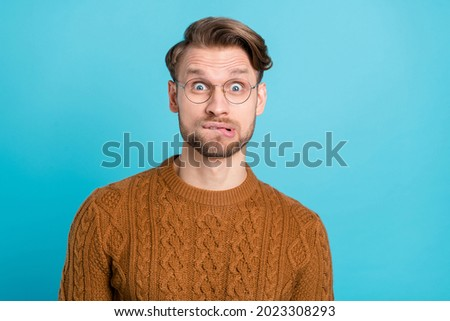 Photo of unhappy troubled young man scared face wear glasses isolated on pastel blue color background