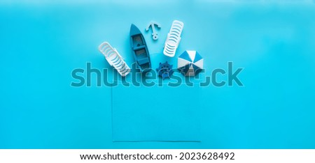 Blue envelope with sun lounger, beach umbrella, boat, anchor, steering wheel inside on a blue background