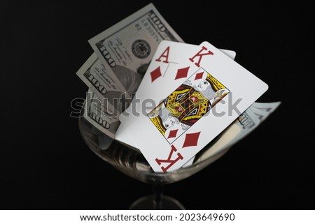Poker Cards King Ace of diamond high card with 300 Dollar bills on black background Cocktail glass Royalty-Free Stock Photo #2023649690