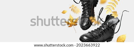 Black flying leather men's or women's boots, autumn golden leaves on light background. Creative concept of autumn shoes. Fashionable stylish hiker boots. Minimalistic footwear Mock up. Unisex boots Royalty-Free Stock Photo #2023663922