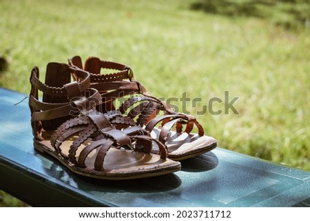A pair of brown sandals sitting on a park bench outside- A pair of girl's brown sandals set on a bench- a pair of brown summer shoes- brown leather sandals Royalty-Free Stock Photo #2023711712