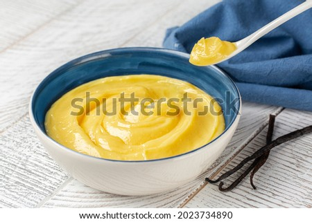 Just made vanilla pastry cream or custard cream. Made with milk, egg yolks and sugar,  thickened with corn starch. White wooden background. Royalty-Free Stock Photo #2023734890